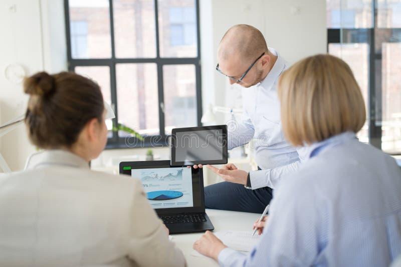Cierre para arriba del equipo del negocio con PC de la tableta en la oficina fotos de archivo