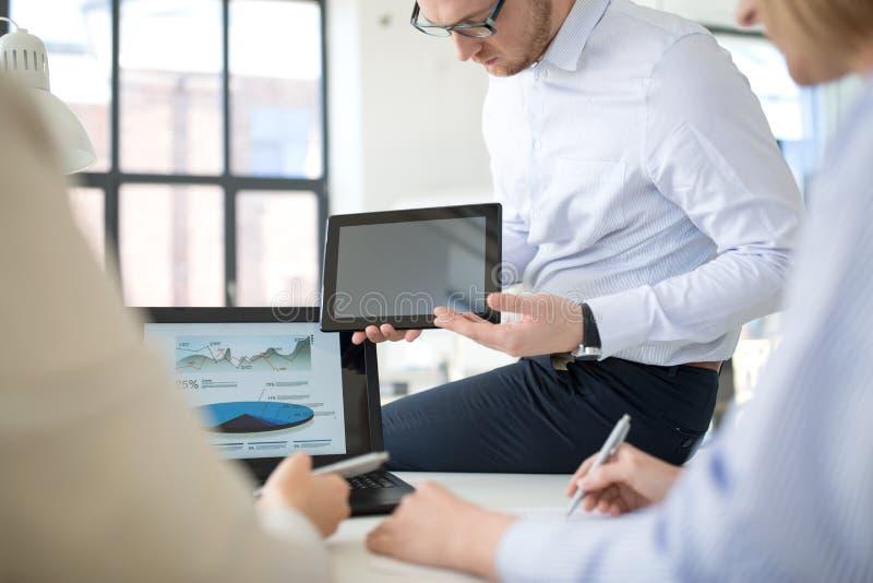 Cierre para arriba del equipo del negocio con PC de la tableta en la oficina imagenes de archivo