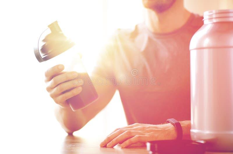 Cierre para arriba del hombre con la botella y el tarro de la sacudida de la proteína foto de archivo libre de regalías