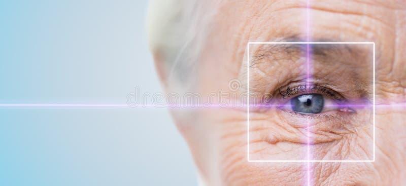 Cierre para arriba del ojo mayor de la mujer con la luz laser imágenes de archivo libres de regalías