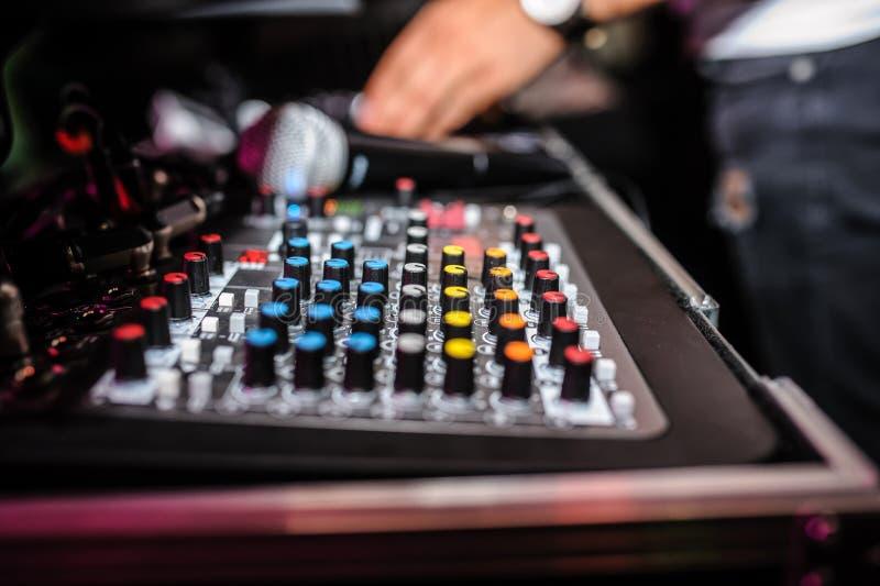 Cierre para arriba del panel de control de DJ que juega música del partido en playe moderno imagenes de archivo