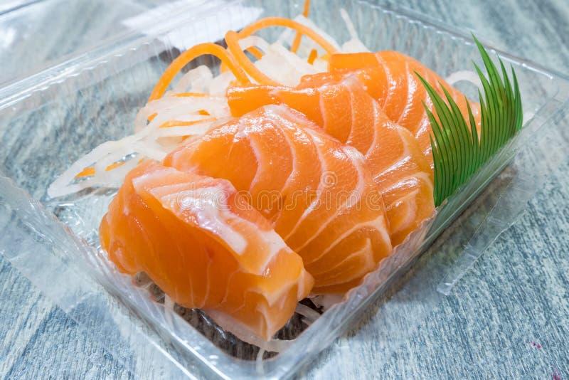 Cierre para arriba del paquete crudo de color salmón del sashimi en caja de plástico transparente en la tabla de madera fotografía de archivo libre de regalías