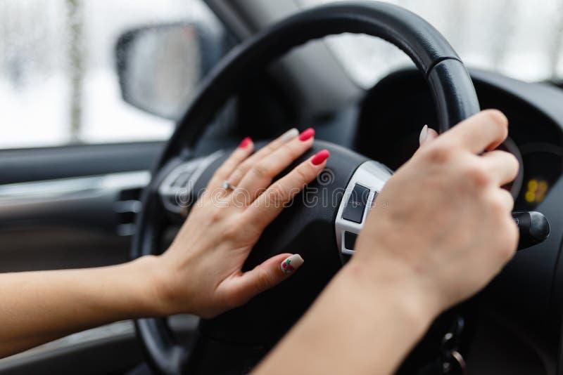 Cierre para arriba del presionado a mano de la mujer el botón de cuerno mientras que conduce a fotografía de archivo libre de regalías