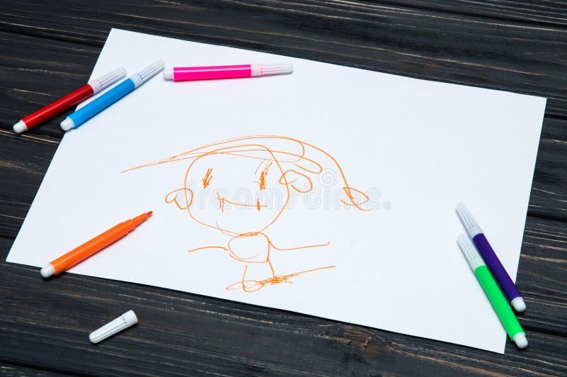 Cierre para arriba Dibujo de un niño de 3 años Tabla negra con una hoja de papel blanca Plumas sentidas coloreadas cerca dispersa imagen de archivo