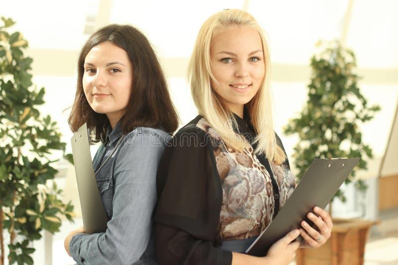Cierre para arriba dos empleados de sexo femenino con un tablero que se coloca en la oficina imagenes de archivo