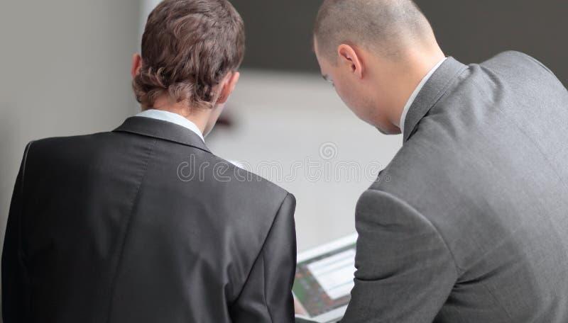 Cierre para arriba dos hombres de negocios que discuten trabajando problemas Visión trasera imagen de archivo