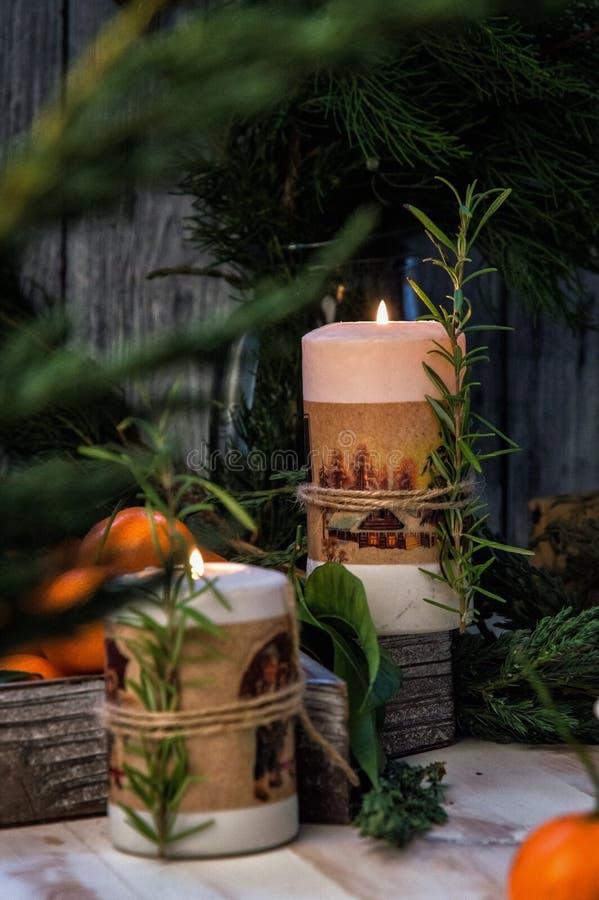 Cierre para arriba Dos velas ardientes de la Navidad, rodeadas por las mandarinas, las ramas del enebro y el romero foto de archivo