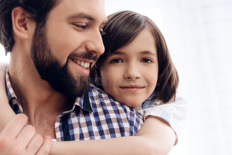 Cierre para arriba El adolescente abraza al padre adulto fotografía de archivo