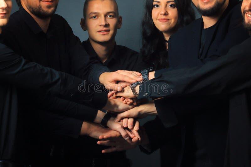 Cierre para arriba el grupo creativo de gente joven dobló sus manos juntas fotos de archivo