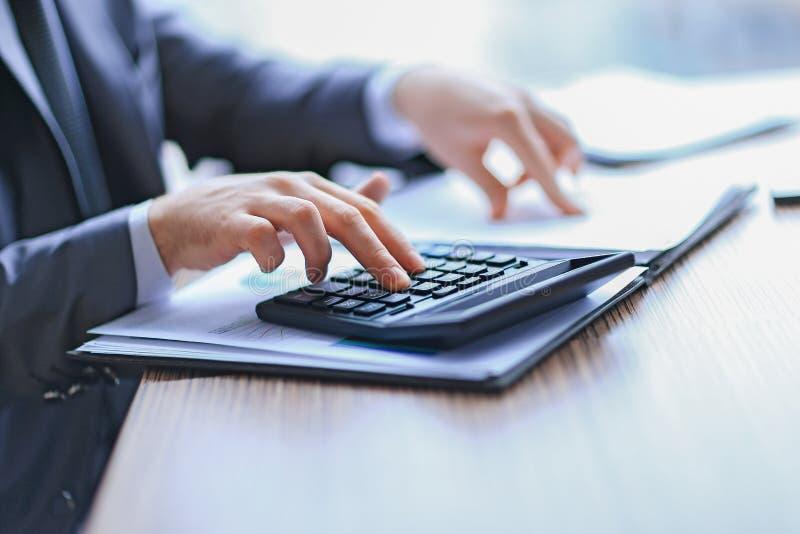 Cierre para arriba el hombre de negocios comprueba los datos financieros con la calculadora imágenes de archivo libres de regalías