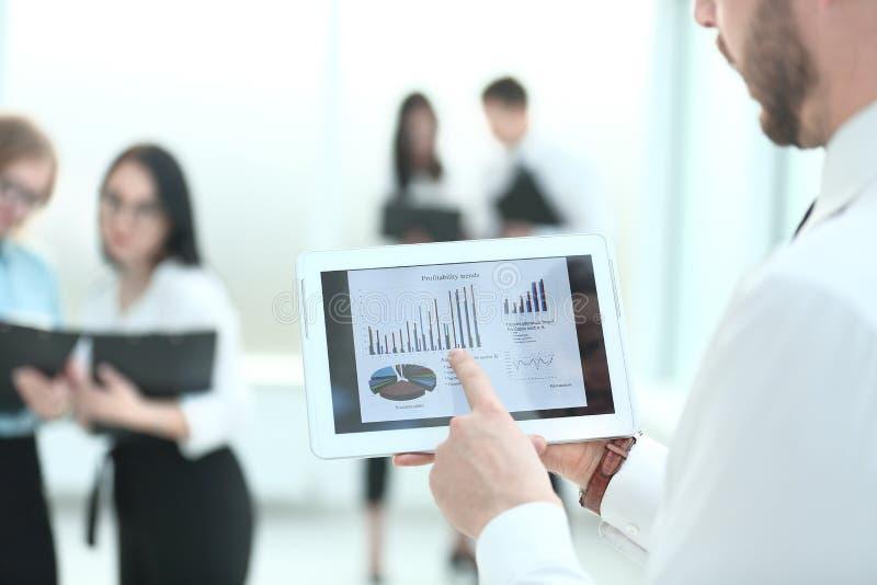 Cierre para arriba el hombre de negocios con la tableta digital, analiza con las cartas financieras imagen de archivo