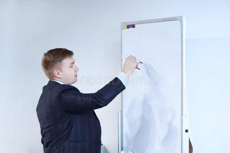 Cierre para arriba el hombre de negocios escribe a un marcador en el tablero foto de archivo
