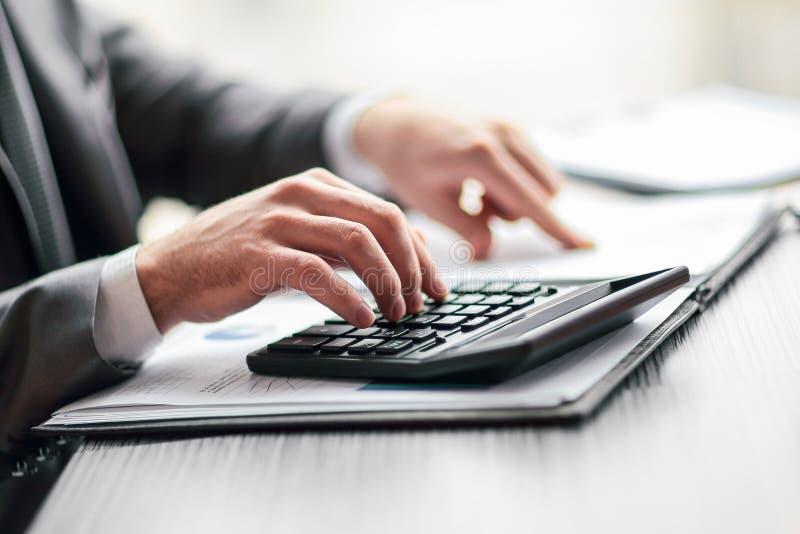 Cierre para arriba el hombre de negocios puede utilizar la calculadora para calcular beneficio fotos de archivo