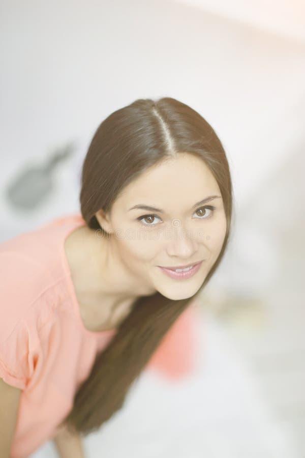 Cierre para arriba el retrato de la mujer joven hermosa en luz empañó el fondo imágenes de archivo libres de regalías