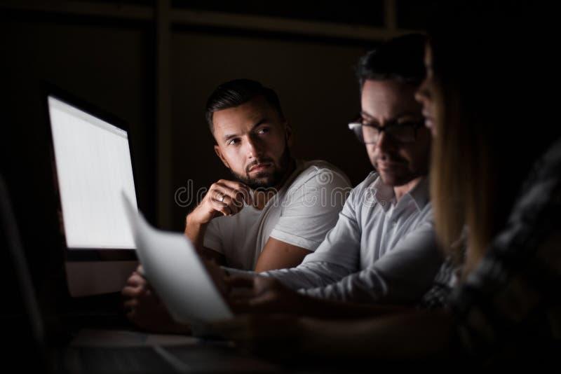 Cierre para arriba empleados cansados que trabajan en horas extras fotografía de archivo