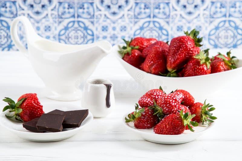 Cierre para arriba Franc?s Provence Fresas jugosas rojas del desayuno con el chocolate Pared de madera blanca de la tabla, azul y fotos de archivo libres de regalías