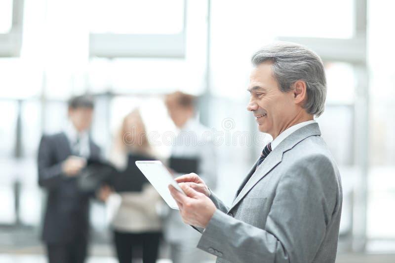 Cierre para arriba Hombre de negocios maduro con la tableta digital en fondo borroso de la oficina foto de archivo libre de regalías