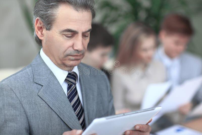Cierre para arriba hombre de negocios moderno que mira la pantalla digital de la tableta foto en fondo borroso de la oficina fotografía de archivo