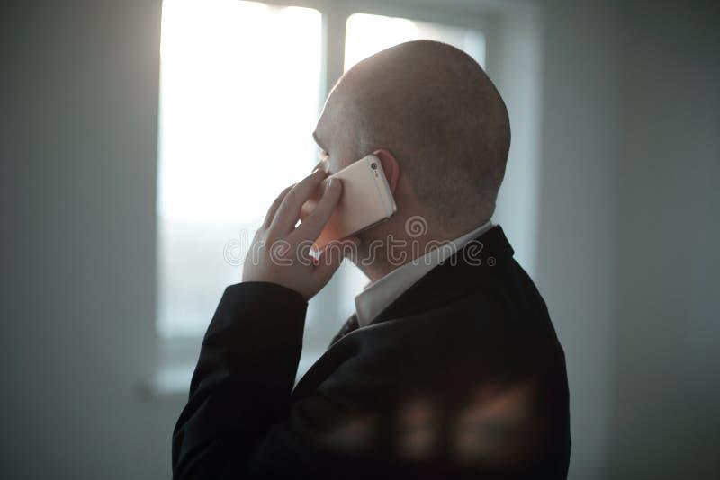 Cierre para arriba hombre de negocios que habla en smartphone, en el fondo borroso de la ventana de la oficina fotos de archivo libres de regalías
