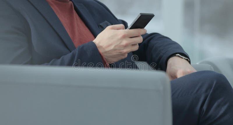 Cierre para arriba hombre de negocios usando el teléfono móvil que se sienta en el pasillo fotos de archivo