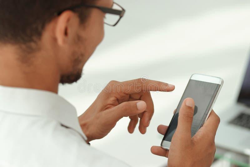 Cierre para arriba hombres de negocios usando un smartphone moderno imagen de archivo