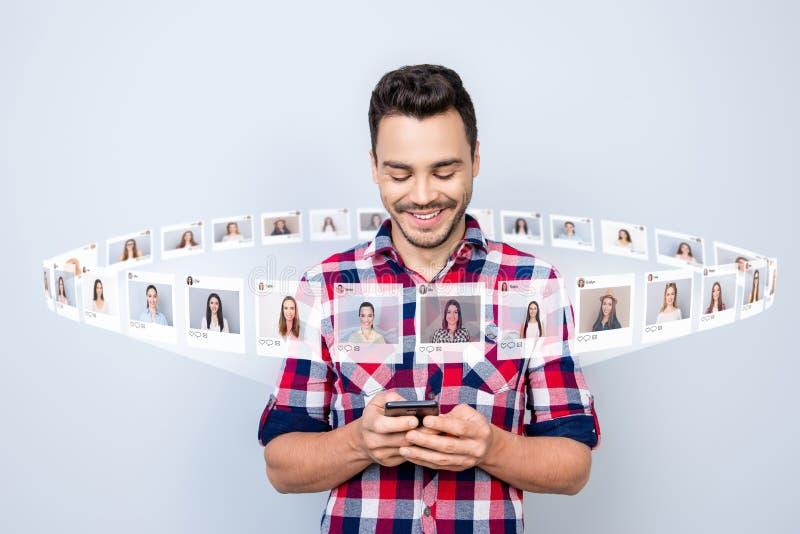 Cierre para arriba la foto alegre él él su teléfono del control del individuo que hace que la charla arregle Internet de la cita  foto de archivo