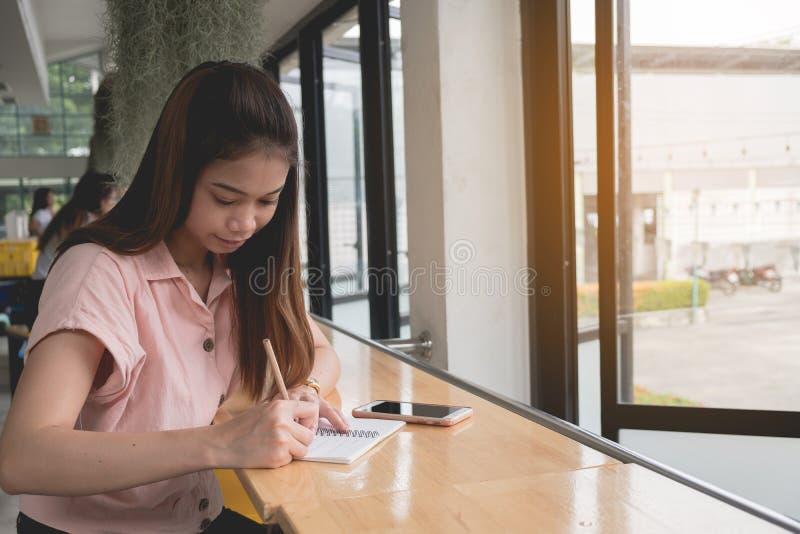 Cierre para arriba La mano de la mujer est? escribiendo en la libreta con el l?piz al lado de la ventana Concepto de trabajo del  fotografía de archivo