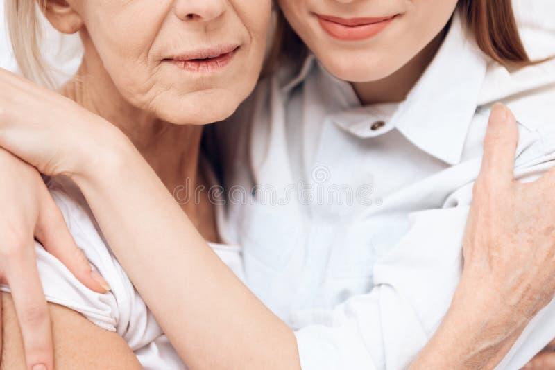 Cierre para arriba La muchacha está cuidando a la mujer mayor en casa Se están abrazando imagenes de archivo