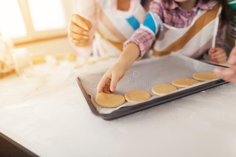 Cierre para arriba La muchacha, su madre y la abuela cocinan las galletas hechas en casa La muchacha pone las galletas en un mold fotos de archivo libres de regalías