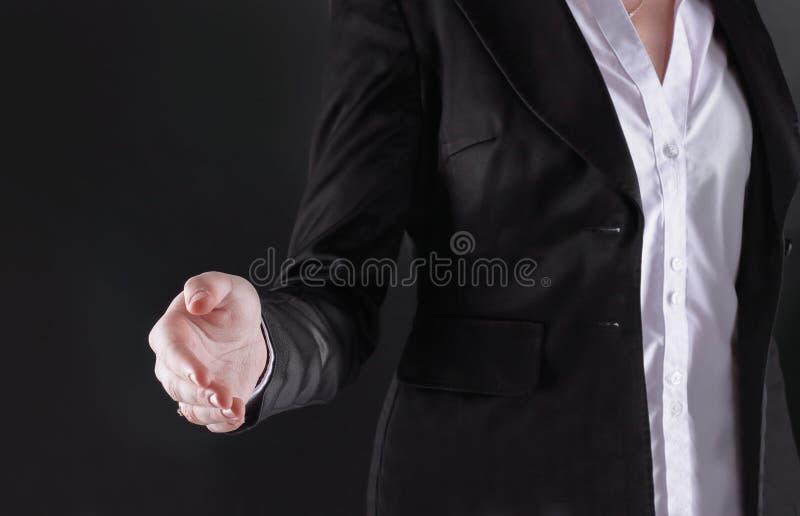 Cierre para arriba la mujer de negocios estira hacia fuera su mano para el apret?n de manos Aislado en fondo negro fotografía de archivo