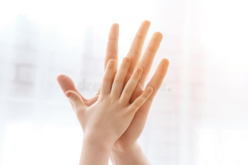 Cierre para arriba La palma del niño da cinco a la palma del varón adulto foto de archivo