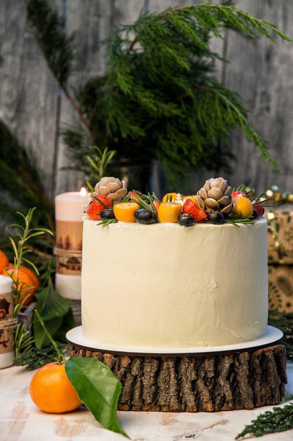 Cierre para arriba La torta del Año Nuevo, diversas bayas adornadas Fondo de madera gris, ramas de los junipes fotografía de archivo libre de regalías
