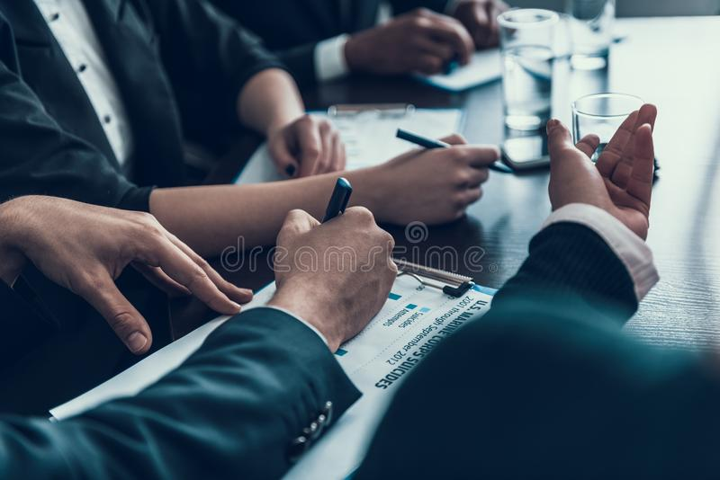 Cierre para arriba Las manos masculinas escriben por la pluma en el papel Reunión de negocios Encuentro en la sala de reunión foto de archivo