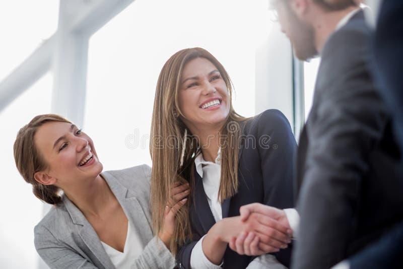 Cierre para arriba mujer de negocios sonriente que sacude las manos con los socios imagen de archivo