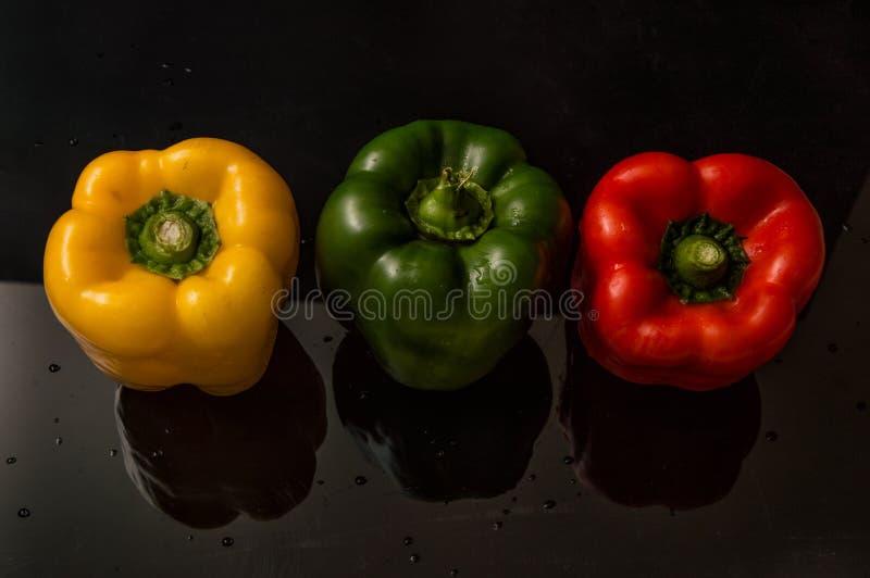 Cierre para arriba Paprika colorida viva de las pimientas dulces Fondo negro fotos de archivo