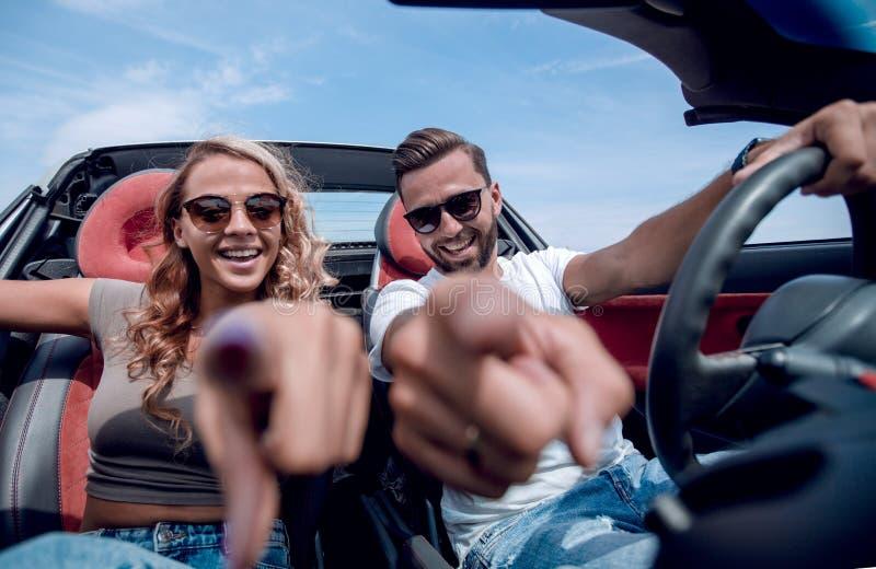 Cierre para arriba pares felices que se sientan en el coche y que se?alan en usted imagen de archivo libre de regalías