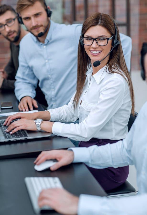 Cierre para arriba personal joven del centro de atención telefónica que se sienta en el escritorio imagen de archivo libre de regalías