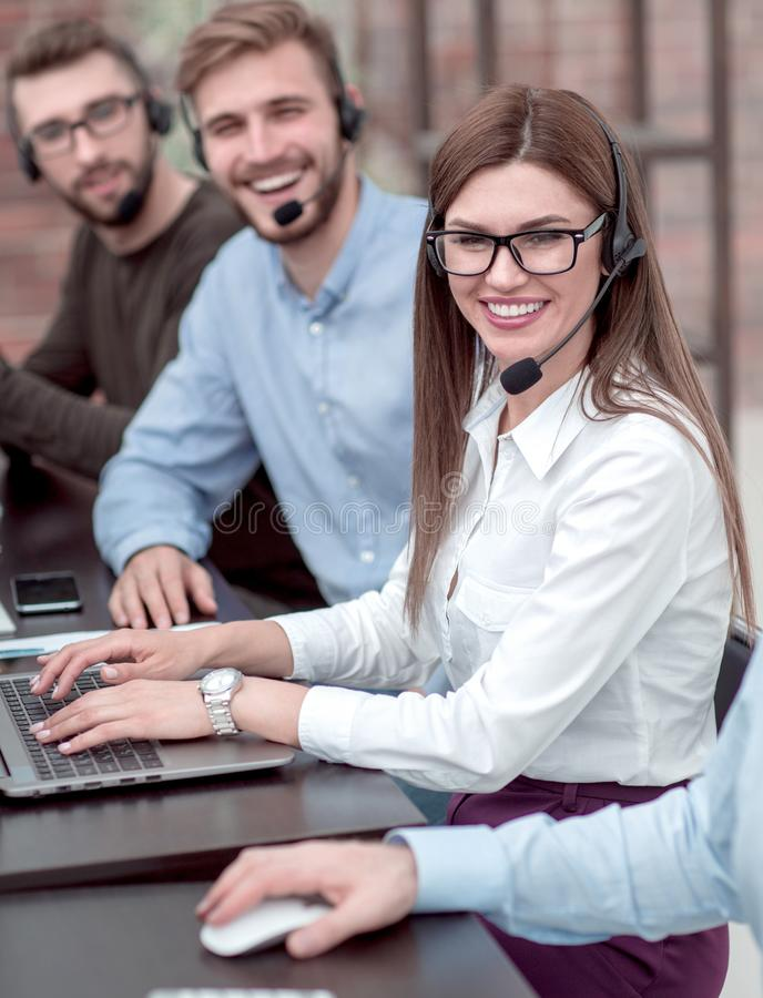 Cierre para arriba personal joven del centro de atención telefónica que se sienta en el escritorio imágenes de archivo libres de regalías