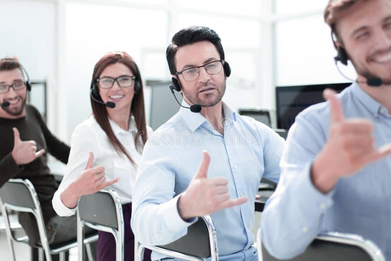 Cierre para arriba personal sonriente del centro de atención telefónica que muestra el pulgar para arriba imagen de archivo libre de regalías