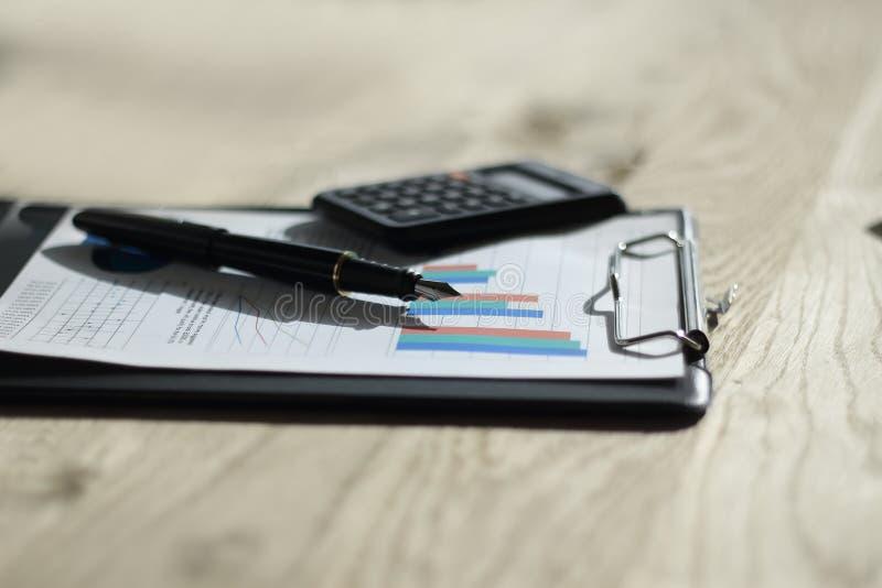 Cierre para arriba pluma, calculadora y tablero en la tabla de madera Concepto del asunto fotografía de archivo libre de regalías