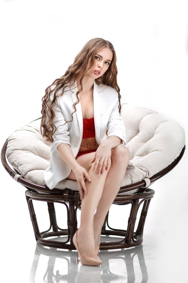 Cierre para arriba retrato de la mujer joven atractiva en la ropa interior que se sienta en silla papasan fotos de archivo