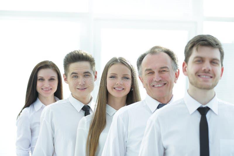 Cierre para arriba un grupo de empleados acertado que se colocan en fila foto de archivo