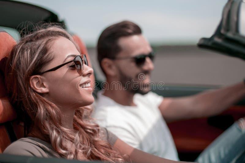 Cierre para arriba una mujer joven con su novio en un coche convertible imagen de archivo libre de regalías
