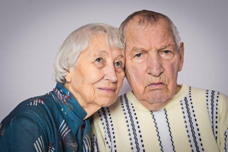 Cierre que se sienta de los pares mayores tristes románticos junto fotos de archivo libres de regalías