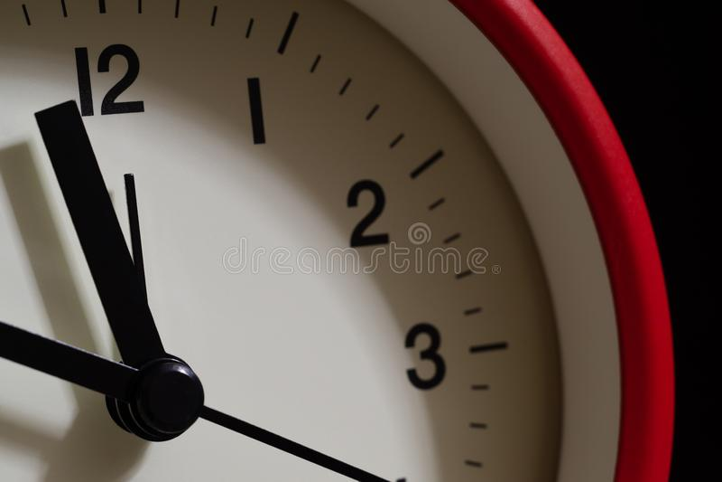 Cierre rojo del despertador para arriba It' s que muestra diez minutos a doce o' c foto de archivo