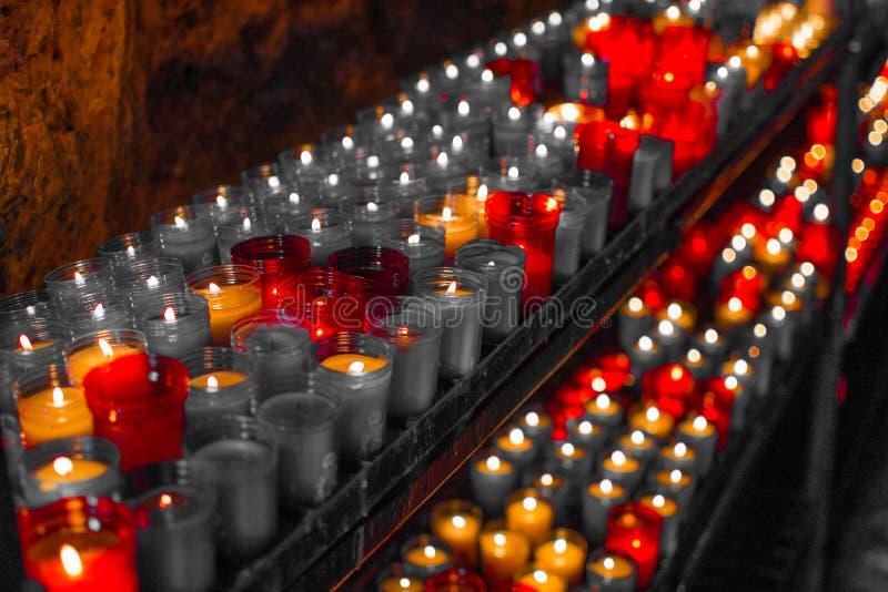 Cierre rojo desaturado para arriba de velas coloridas en una escena espiritual oscura Conmemoración, entierro, monumento Simbolis foto de archivo libre de regalías