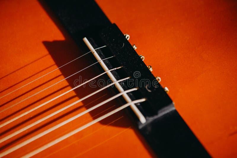 cierre rojo marrón de la guitarra acústica encima de la macro fotografía de archivo