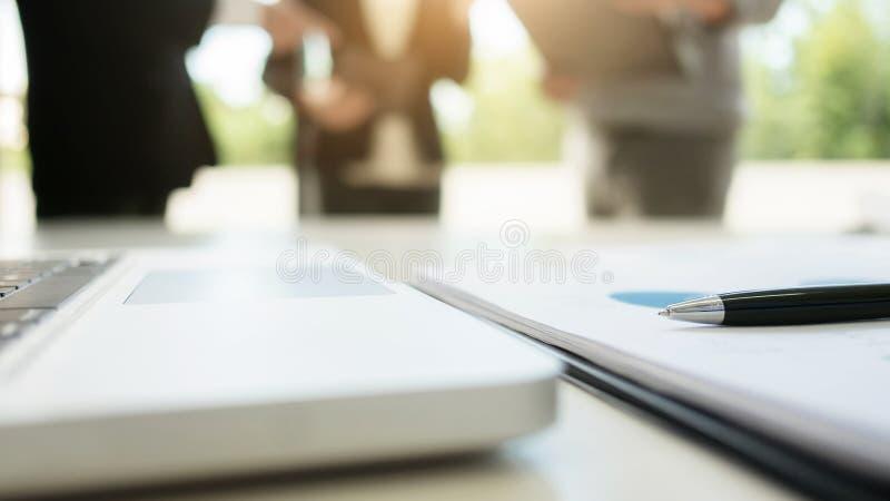 Cierre-tiro de la exhibición y de datos financieros, tres ejecutivos de operaciones de un ordenador que se colocan en el fondo fotografía de archivo