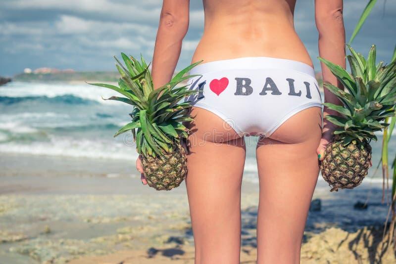 Cierre tropical atractivo del extremo de la mujer para arriba con la fruta exótica de la piña en la playa de la isla del paraíso  fotografía de archivo libre de regalías