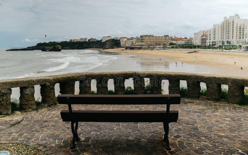 Cierre vacío del banco de madera para arriba en paisaje marino escénico en la costa costa atlántica en el cielo azul, Biarritz, p fotografía de archivo libre de regalías